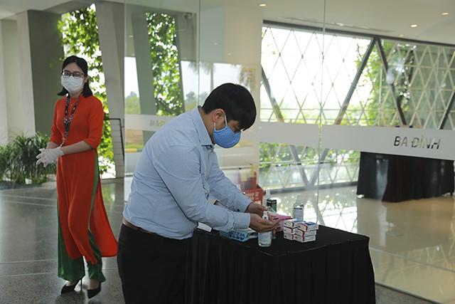 Các cổ đôngđều đeo khẩu trang và rửa tay diệt khuẩn trước khi vào phòng họp.